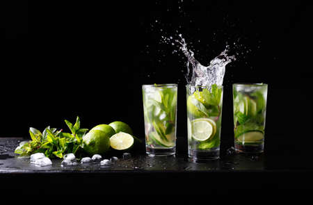 Mojito zomer strand verfrissende tropische cocktail non-alcoholische drank in highball glas met splash soda water, limoensap, muntblaadjes, suiker, ijs en rum. Donkere zwarte achtergrond met kopie ruimte tekst