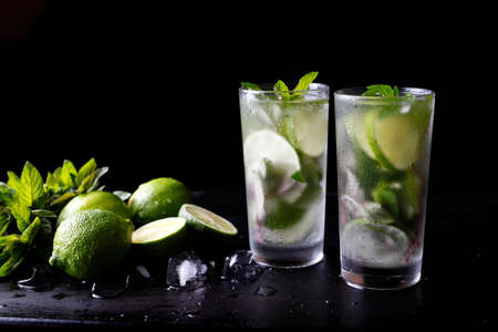Mojito traditionele zomer vakantie verfrissende cocktail alcohol drinken in glas, bar voorbereiding soda water drank, limoensap, muntblaadjes, suiker en rum. Donkere zwarte achtergrond met kopie ruimte tekst Stockfoto