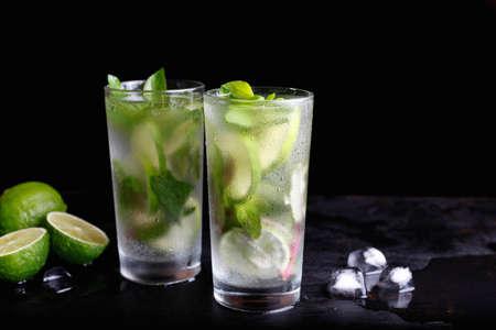 Mojito zomervakantie verfrissende tropische cocktail non-alcoholische drank in glas, frisdrank water drank, limoensap, muntblaadjes, suiker, ijs en rum. Donkere zwarte achtergrond met kopie ruimte tekst
