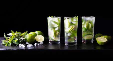 Drie glazen cocktail mojito limonade op de bar. Cocktail van de Verfrissende Partij. Kalk, ijs en munt op de tafel. Zwarte achtergrond. Stockfoto