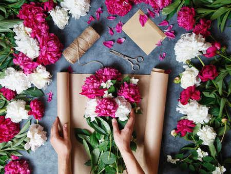Vrouwelijke bloemist die mooi boeket maakt bij bloemwinkel. Bloemist op het werk: mooie vrouw die zomerboeket van pioenen op een werkende grijze lijst maakt. papier, schaar, envelop op tafel.