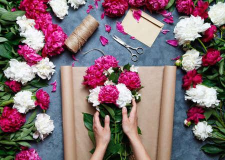 Bloemist op het werk: mooie vrouw die zomerboeket van pioenen op een werkende grijze lijst maakt. papier, schaar, envelop voor felicitaties op de tafel. Uitzicht van boven. Plat leggen samenstelling.