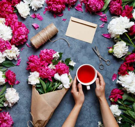 Plat leggen zomer bloemachtergrond. Een boeket bloemen van pioenrozen, de handen van vrouwen en houd een kopje karkade-thee. Touw, papier, schaar en envelop voor felicitaties op de tafel.
