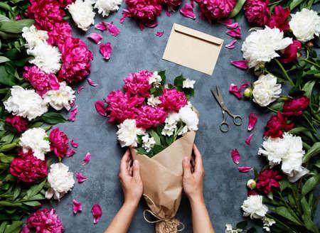 Vrouwelijke bloemist die mooi boeket houdt bij bloemwinkel. Bloemist op het werk: mooie vrouw die zomerboeket van pioenen op een werkende grijze lijst maakt. papier, schaar, envelop voor felicitaties. Stockfoto