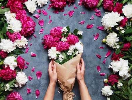 Bovenaanzicht van handen van jonge vrouw bloemist bedrijf mooi boeket van pioenen. Bloemist op het werk: mooie vrouw die zomerboeket van pioenen maakt op een werkende grijze tafel. Flat lay samenstelling.