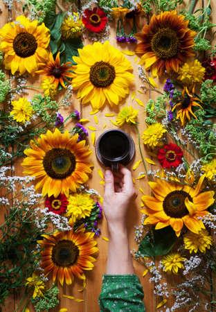 Bloemen zomer achtergrond. Een mok koffie in de hand van een vrouw op een houten achtergrond met zonnebloemen en wildflowersbloemen. Hallo zomer juli, augustus. Aankomst in de zomerstemming. Plat leggen.