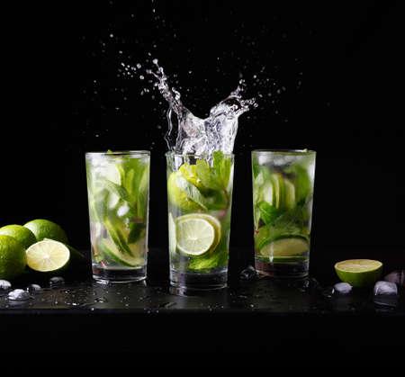 Mojito traditionele strand verfrissende cocktail alcohol drinken in glas met splash, bar voorbereiding soda water, limoen, muntblaadjes, suiker en rum. Donkere zwarte achtergrond. Vierkant formaat frame Stockfoto