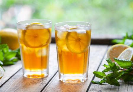 IJsthee met plakjes citroen op houten tafel met het oog op het terras. Koude longdrink of limonade. Close-up zomer vitamine antioxidant drank. Een bevroren glas. Ruimte voor tekst kopiëren.