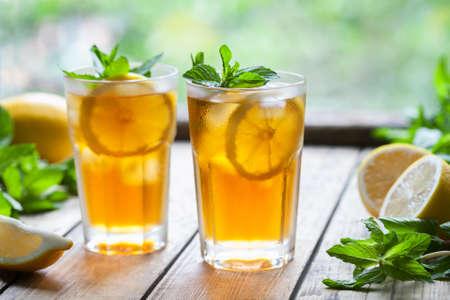 Ijsthee thee met citroenplakken en munt op houten tafel met uitzicht op het terras en de bomen. Close-up zomer vitamine antioxidant drank. Een bevroren glas. Ruimte voor tekst kopiëren. Koude longdrink of limonade