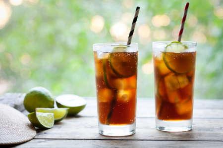 Twee glazen Cuba Libre of lange eiland iced tea cocktail met een cola, ijs, limoen, rum met rietjes op houten tafel met het oog op het terras. Sluit omhoog de zomerdrank. Koude longdrink of limonade.