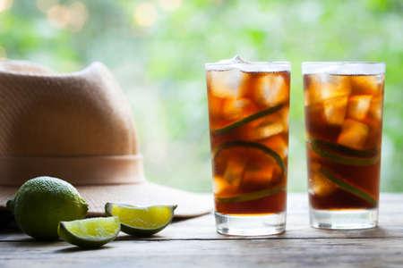 쿠바 리브레 또는 긴 섬 아이스 티 라임, 콜라, 얼음, 민트와 럼 나무 테이블 밀 짚 모자와 테라스에보기와 칵테일. 여름 음료를 닫습니다. 콜드 긴 음료