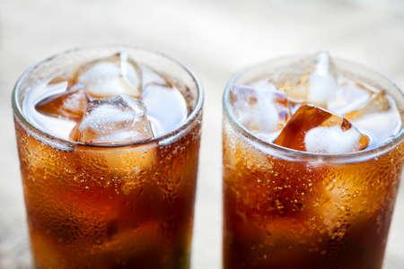 Twee glazen cola met ijs. Close-up van een verfrissend drankje. Stockfoto