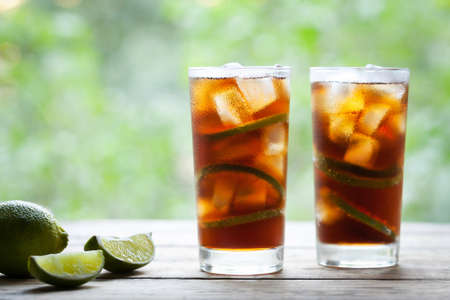 Twee glazen Cuba Libre cocktail met limoen, ijs en munt op houten tafel met uitzicht op het terras. Sluit omhoog de zomerdrank. Ruimte voor tekst kopiëren. Koude longdrink of limonade.