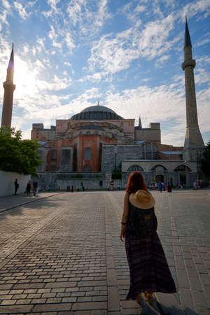Toeristische vrouw in de buurt van Hagia Sophia moskee beroemde reizen religie mijlpaal islam Turkse architectuur gebouw, oude kerk basiliek kathedraal museum buitenkant Aya Sofia of Sofya. Turkije Istanbul Fatih. Stockfoto