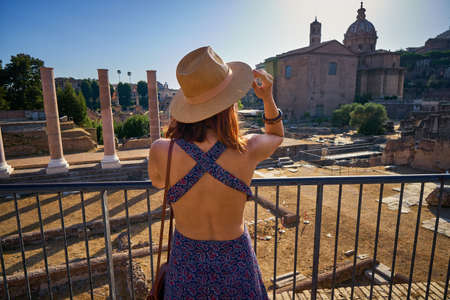 Young woman tourist looking at Roman Forum famous ancient history roman empire architecture heritage monument travel historical and cultural landmark in Rome Italy