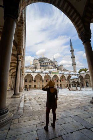 Young woman tourist in Blue Mosque Sultanahmet interior view roof Turkish architecture