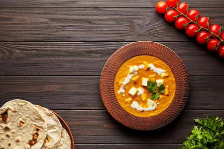 Shahi paneer traditional Indian vegetarian food with vegetables and butter paneer cheese on dark wooden Stockfoto