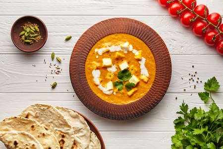 Shahi paneer traditional Indian vegetarian masala gravy meal vegetables, white sauce and butter paneer in clay bowl Stockfoto