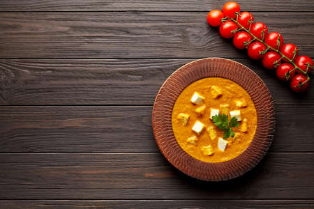 Shahi paneer traditional Indian vegetarian  meal with vegetables and paneer cheese on dark wooden