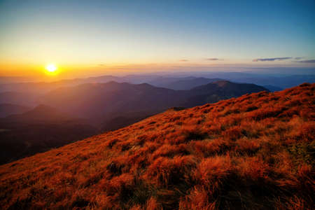 Sunset over the mountain peaks and hills panorama with colorful grass