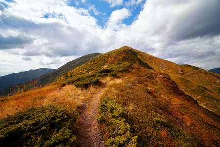 Beautiful hiking path in mountains peaks and hills with yellow grass outdoor view