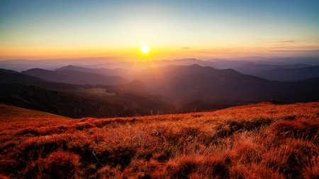 Beautiful vibrant sunset over the mountain peaks and hills panorama with colorful grass