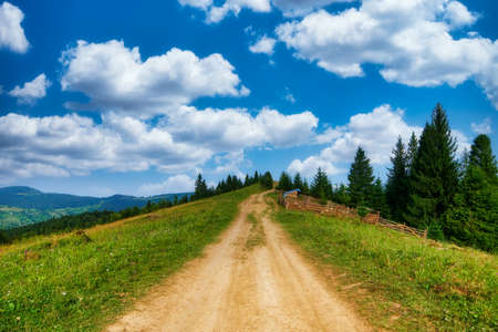 Rural path in mountains nature field summer meadow road landscape panorama beautiful hill countryside outdoor tourism hiking or trekking way Archivio Fotografico
