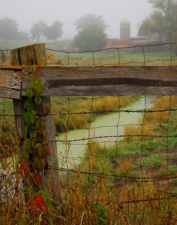 fenceline: fenceline and post in rain and fog with farm in background