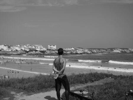Young man with the wetsuit lowered contemplates Peniche beach after a surfing session on a hot summer day