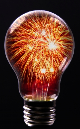 Creative Explosion as a fireworks display celebration represented by exploding sparks of color in the shape of a light bulb on black as a concept of innovation and creative power.