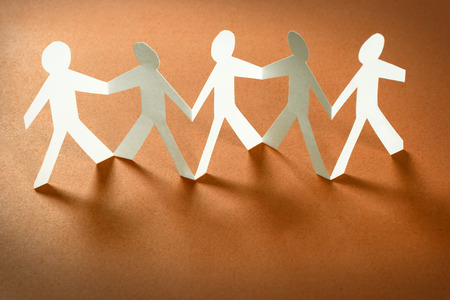 Group of paper people holding hands. Teamwork concept Stock Photo