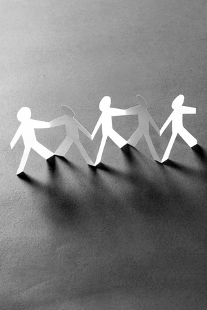 Group of paper people holding hands. Teamwork concept photo