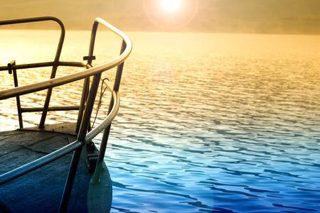 the clear sky: la salida del sol sobre el lago de montaña y el barco Foto de archivo