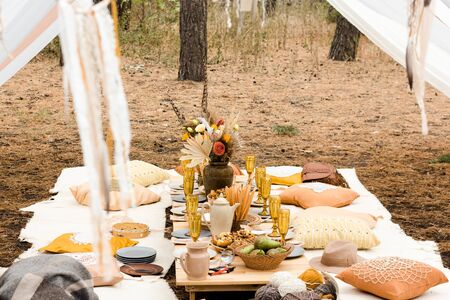 Table prepared for lunch in autumn nature of a pine forest. Autumn picnic in the forest. on the table is a teapot with tea, pie, baked apples, yellow glasses, a bouquet, plates