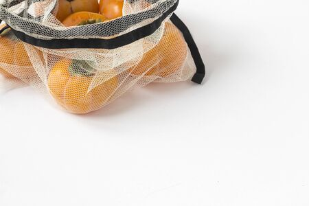 Fruits in reusable textile grid bag on white wood bacground. Zero waste shopping, storage and recycling concept, eco friendly lifestyle, orange persimmon close up,place for text Stock fotó