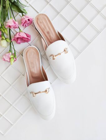 Trendy blog or magazine concept. White female loafers without heels on a white background with pink eustoma flowers. Flat lay, top view minimal background.