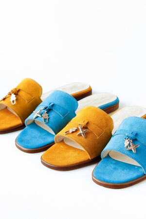 Stylish womens spring or summer shoes, flip flops of different colors on a white background. yellow pigeons for walking along the beach. place for inscription