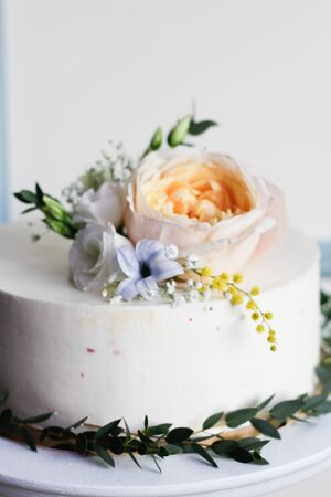 a white cake decorated with flowers and herbs stands on a wooden table in a restaurant at a wedding.