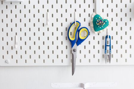 tools for working in the sewing workshop scissors, a needle case with needles hanging on a peg board, as an idea for storage in a craft room or workshop.place for inscription Standard-Bild