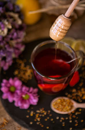 grippe: dripping sweet honey on cup of tea close-up background