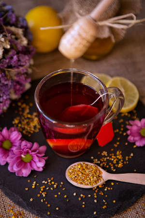 health, traditional medicine, folk remedy concept - dripping sweet honey on cup of tea background