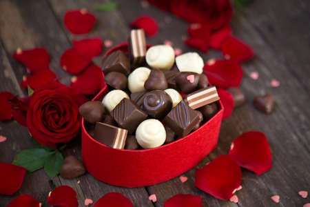 Gift box with red roses and sweet chocolates on wooden background Standard-Bild