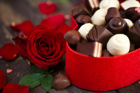 Chocolates in heart shaped box and red roses on wooden background- Mother�s Day Banco de Imagens
