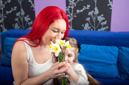 Happy mom with her daughter receives flowers Stock Photo