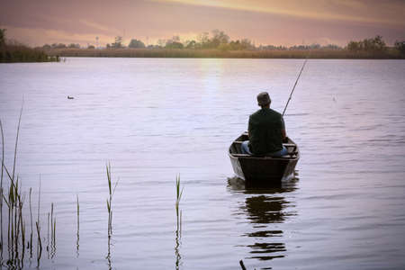 fishing-Fisherman on boat in river at sunset