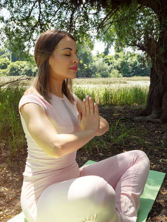 yoga and relax - young woman in nature in yoga pose Stock Photo