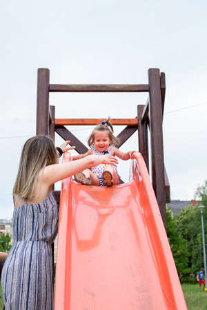 happy little girl on slide at playground Stock Photo