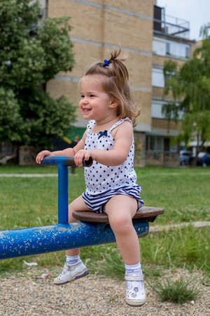 Little girl playing on teeter in the playground