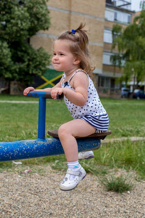 little child playing on teeter at playground Stock Photo