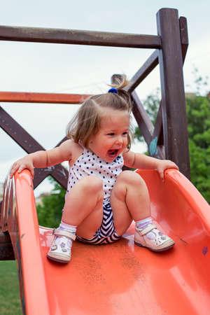 smiling girl sliding down on slide at playground